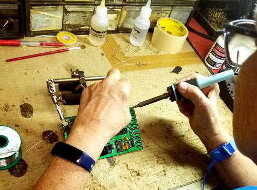 technician soldering on circuit board